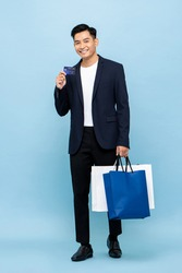 Handsome southeast Asian man holding  shopping bag and credit card for cashless payment concept in isolated studio light blue background