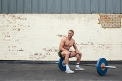 Handsome sportive man sitting on barbells, resting after workingout