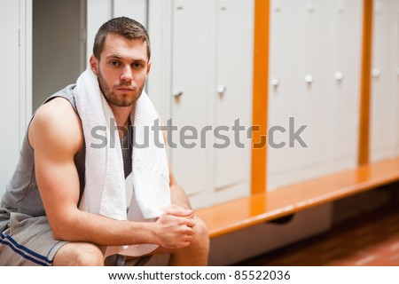Handsome sports student sitting on a bench with a towel - stock photo