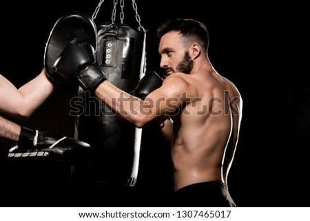 handsome sportsman fighting with man in punching gloves isolated on black