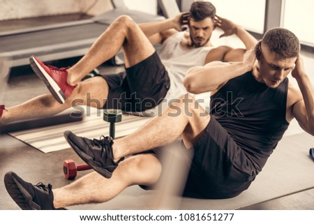 handsome sportsmen doing sit ups together in gym
