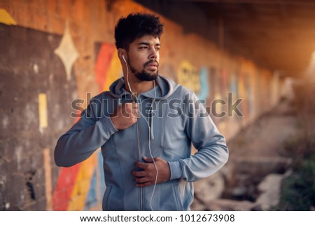 Handsome sporty active afro american bearded man with earphones standing outside on abandon place and holding zipper with one hand while looking far away.