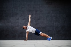 Handsome sporty caucasian man in shorts and t-shirt stretching his arm in plank position in front of gray wall.