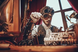 Handsome steampunk man scientist inventor works in his laboratory with Victorian interior.