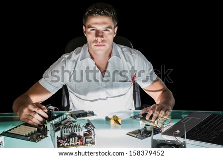 Handsome stern computer engineer working by night at his lit desk
