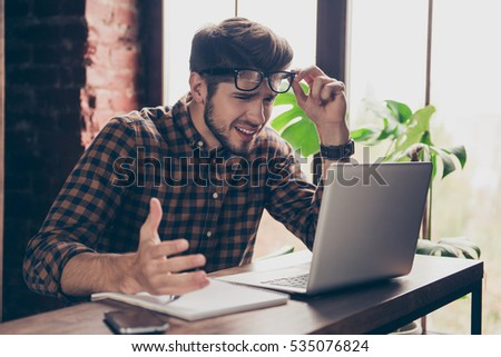 Handsome stressed  young man in glasses using  laptop #535076824