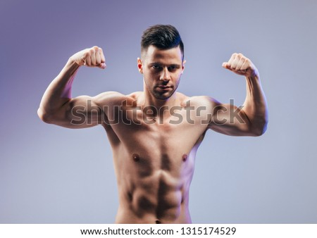 Handsome strong bodybuilder athletic man flexing his muscles. Sport concept
