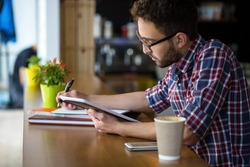 Handsome student man looking at tablet PC and writing essay or publication with hand. Man in glasses studying in restaurant.