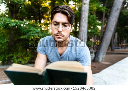 Handsome student reads a book concentrated in an outdoor park.