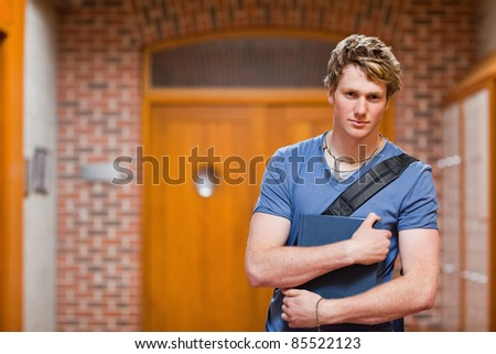 Handsome student with a book in a corridor