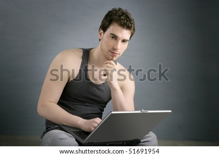 handsome student young man sit working on laptop over gray background