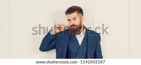 Handsome stylish bearded man. Men's beauty, fashion. Male beard and mustache. Sexy male, macho, long beard. Studio portrait of a bearded hipster man. Bearded man in suit and bow-tie. Copy space.