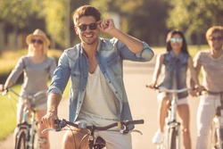 Handsome stylish guy is looking at camera and smiling while cycling with his friends in the park