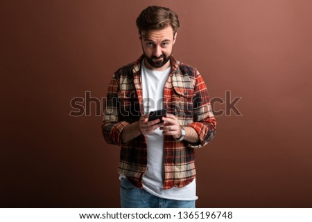 handsome stylish hipster bearded man on brown background holding using smartphone, texting, isolated in vintage checkered shirt, looking in camera with funny face expression