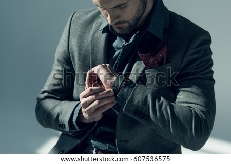 Handsome stylish man adjusting smartwatch on grey