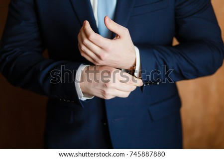 Handsome stylish man dressed in modern formal clothes buttoning jacket. Close up of hands of guy in blue jacket, white shirt. Person ready for wedding celebration, graduation or business meeting.  #745887880