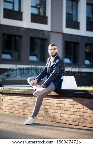 Handsome stylish man. Handsome stylish man wearing glasses sitting outside near the office building
