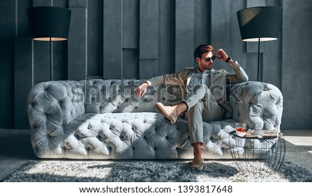 Handsome stylish man in beige suit at home sitting on sofa.