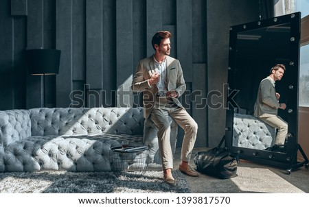 Handsome stylish man in beige suit at home sitting on sofa near mirror.