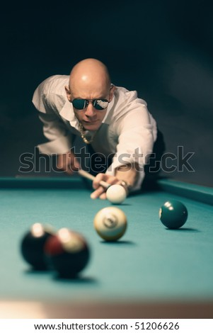 Handsome stylish man playing pool billiards, selective focus on face