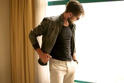Handsome stylish man posing outdoor at hotel near the window,young travel businessman waiting for his lunch at hotel room,successful male on his 30th,man,leather black jacket,male fashion,cozy clothes