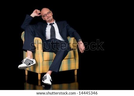 Handsome successful middle aged businessman with spectacles, studio shot, black background