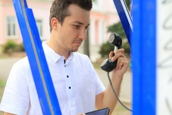 Handsome surprised man in a white shirt with a handset from a payphone in his hands.