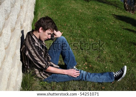 handsome teen boy by stone wall - stock photo