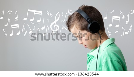 Handsome teen boy listening to music on headphones over grey background