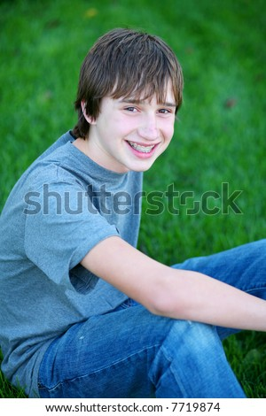 handsome teen guy model seated in grass smiling