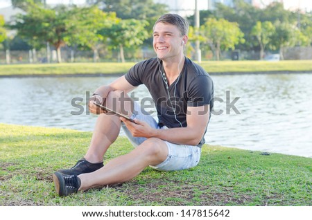 Handsome teen using white earphones and listening to music in a park outdoors