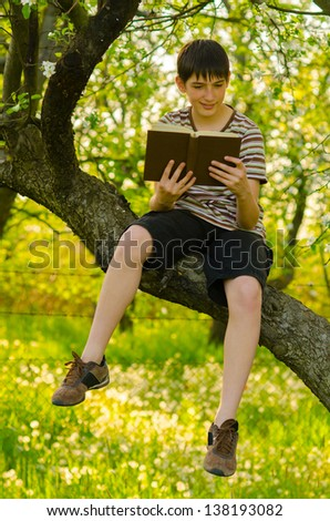 Handsome teenage boy sitting on the tree and reading old book on sunny spring day.