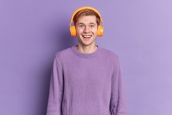Handsome teenage boy smiles gladfully wears jumper stereo headphones listens pleasant melody isolated over purple background. Glad meloman enjoys favorite song. People and lifestyle concept.