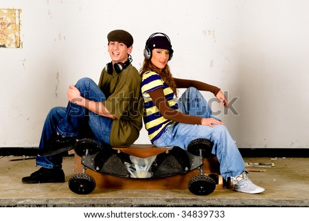 Handsome teenager couple casual dressed, hip hop urban culture.  ** note : slight motion blur in female legs. - stock photo