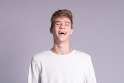 Handsome teenager guy 16-18 years old smiling and looking at the camera over gray background. Close up emotional portrait of caucasian young man