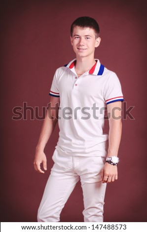 Handsome teenager in casual wear posing in studio. Stylish smiling male model. Happy boy in fashion T-shirt waiting for girlfriend. thoughtful man wearing stylish watch