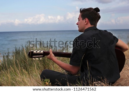 Handsome teenager with an acoustic guitar sitting on the grass near the beach, carefree guy looking dreamily at sea shore, summer evening, summertime vacation outdoor  #1126471562