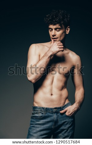 handsome tender man in jeans posing isolated on dark grey