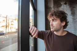 Handsome thoughtful guy in brown sweetshirt staring at the window