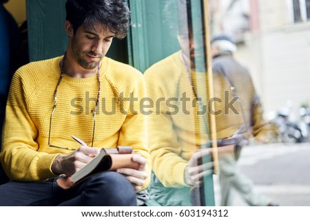 Handsome thoughtful male writer noting best ideas for magazine article about restaurant review planning strategy in personal diary organizing ideas to create successful material for front page #603194312