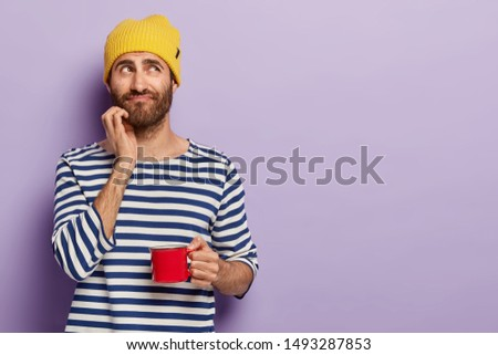 Handsome thoughtful young man with bristle, holds mug of coffee, has pensive look, break after work, wears striped jumper, yellow headgear, isolated over purple wall, blank space on right side