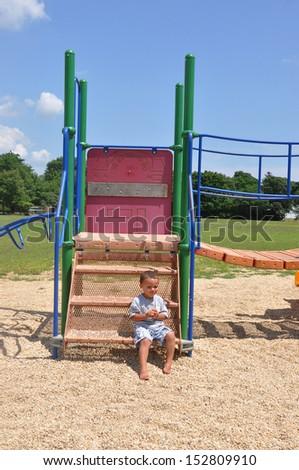 Handsome Toddler Boy sitting Thinking on Playground Equipment Sunny Blue Sky Day Suburban Residential Neighborhood