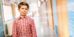 Handsome toddler child with green eyes feeling disgusted with tongue out at school corridor