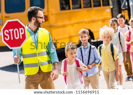handsome traffic guard crossing road with pupils in front of school bus #1156696915
