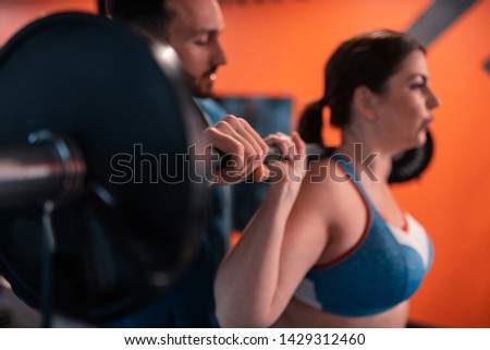 Handsome trainer helping. Close up of handsome trainer helping woman with lifting barbell in the fitness center