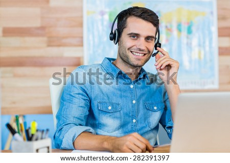 Handsome travel agent smiling at camera in the office