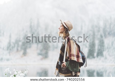 Handsome traveling woman enjoying wilderness in front of incredible mountain lake. Wearing hat, poncho and backpack. Winter is coming, first snowfall. Wanderlust and boho style #740202556