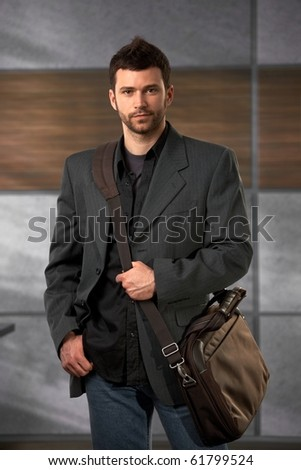 Handsome trendy office worker standing in lobby holding laptop bag looking at camera confidently.