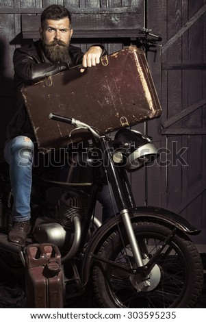 Handsome unshaven male biker in leather jacket sitting near motorcycle in garage with big brown old briefcase and rusty fuel can looking forward on workshop background, vertical picture #303595235