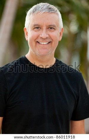 Handsome unshaven middle age man in an outdoor setting.